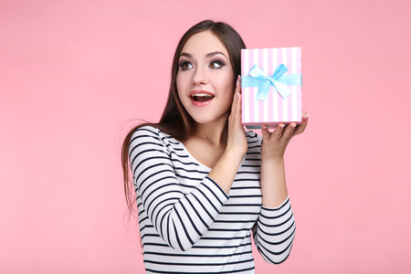 Beautiful young woman with gift box on pink background