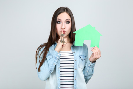 Young woman showing keys and paper house on grey background