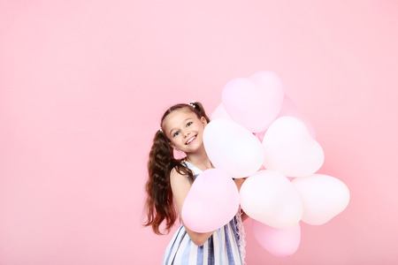 Young girl with balloons on pink background