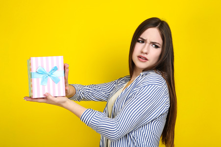 Beautiful young woman with gift box on yellow background Stock Photo