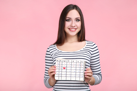Beautiful young woman with calendar on pink background