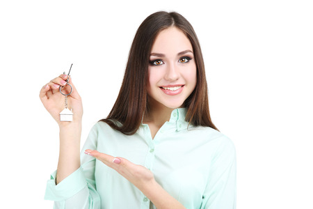 Young woman showing house keys on white background Stock Photo