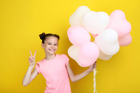 Beautiful young girl with balloons on yellow background