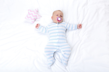 Baby boy with soft star toy sleeping in white bed
