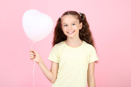 Cute young girl with balloon on pink background