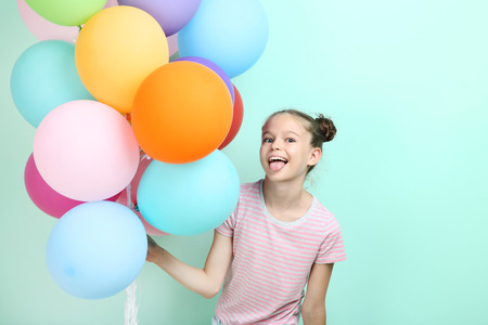 Beautiful young girl with colored balloons on mint background