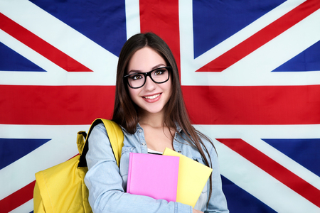 Young student with backpack and books on British flag background