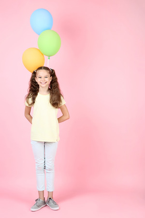 Cute young girl with colored balloons on pink background