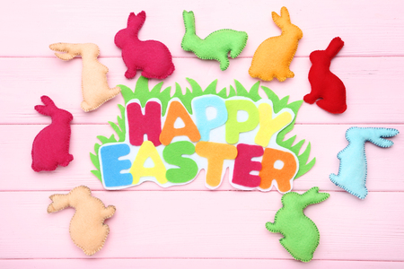 Fabric rabbits with text Happy Easter on pink wooden table