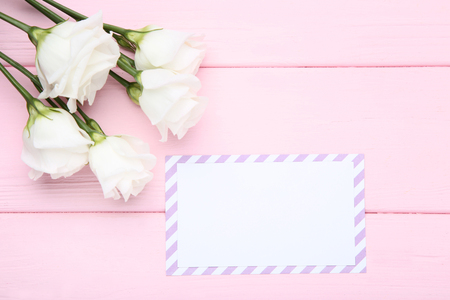Greeting card with eustoma flowers on pink wooden table Stock Photo