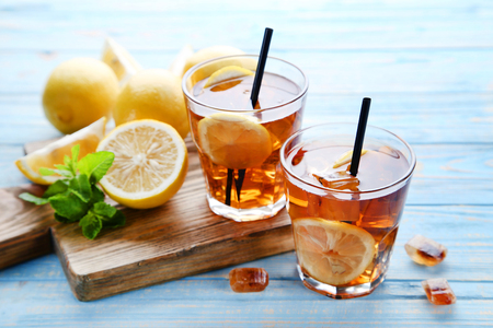 Ice tea in glasses with lemon and mint leafs on wooden table