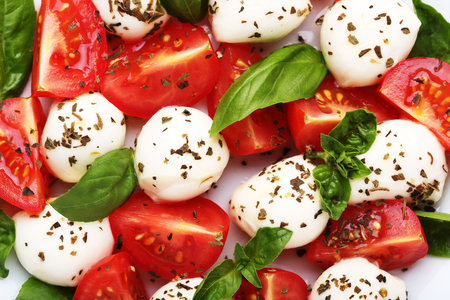 Mozzarella, tomatoes and basil leafs on white plate Imagens