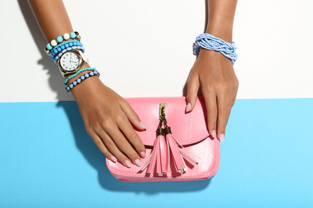 Female hands with bracelets and pink handbag on colorful background Stock fotó - 118542787