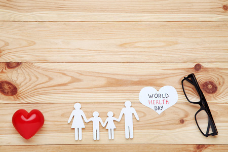 Text World Health Day with family figure, glasses and red heart on wooden table
