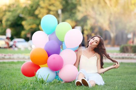 Beautiful girl with colored balloons sitting on green grass Foto de archivo