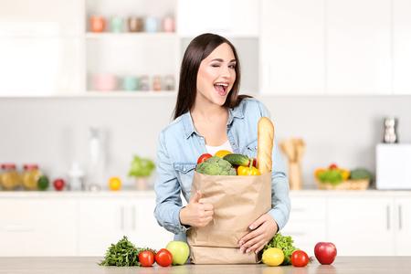 Schöne Frau, die auf der Küche mit Einkaufstüte steht