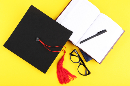 Graduation cap with notepad, pen and glasses on yellow background
