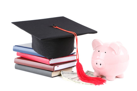 Piggybank with graduation cap, books and dollar banknotes isolated on white background
