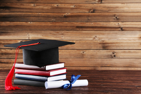 Graduation cap with diploma and stack of books on brown wooden table