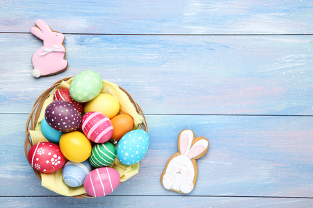 Colorful easter eggs in basket with gingerbread cookies on wooden table