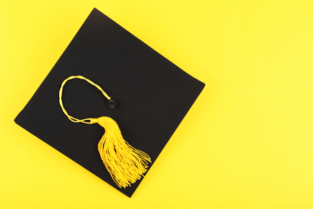 Graduation cap on yellow background