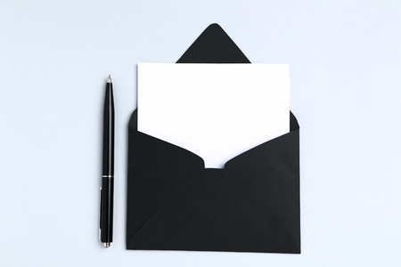 Blank paper with envelope and pen on grey background