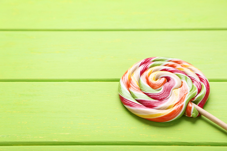 Colorful lollipop on green wooden table Banque d'images