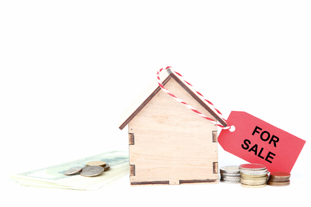 Wooden house model with money and text For Sale isolated on white background Stock Photo