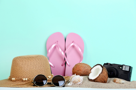 Summer accessories with seashells and coconuts on mint background