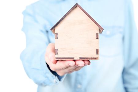 Female hand holding wooden house model Stock Photo