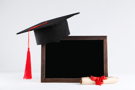 Graduation cap with blank frame and diploma on grey background