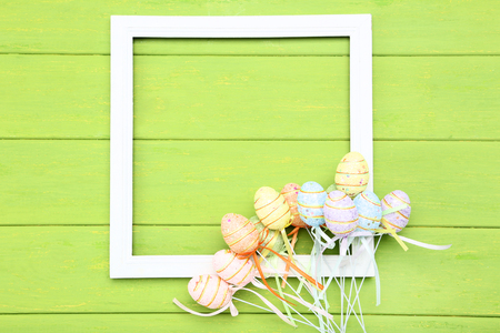 Easter eggs with blank frane on green wooden table Stock Photo