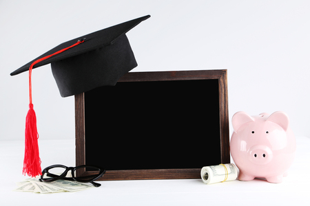 Piggybank with graduation cap, dollar banknotes and blank frame on grey background 写真素材