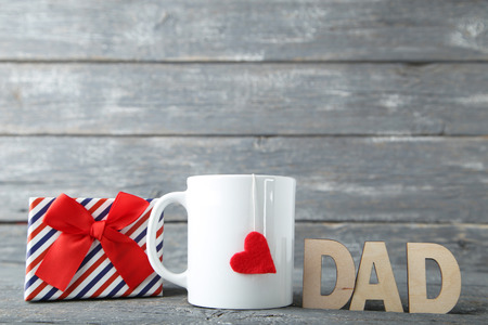 与杯子和礼物盒的父亲节概念在木桌上