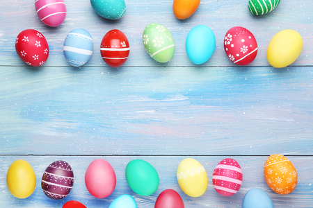 Colorful easter eggs on blue wooden table