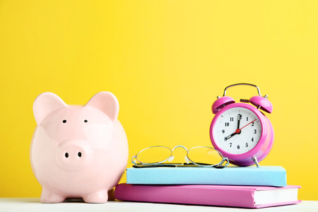 Pink piggy bank with alarm clock, glasses and books on yellow background