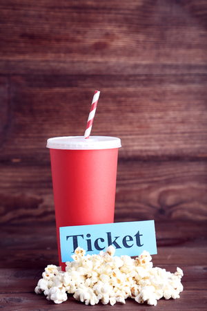 Red paper cup with popcorn and word Ticket on wooden table