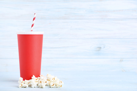 Red paper cup with popcorn on wooden table Banco de Imagens - 120396247