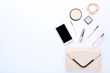 Handbag with cosmetics and smartphone on white background