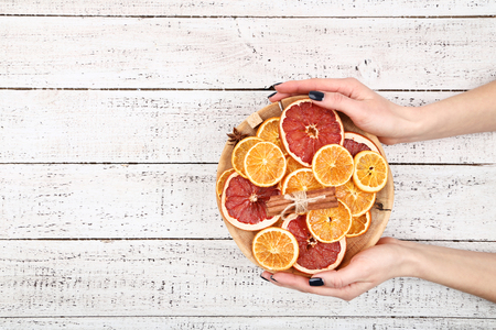 Female's hands holding board with dried citrus fruits, cinnamon, star anise and sugar cubes