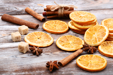 Dried orange fruits with cinnamon, star anise and sugar cubes on brown wooden table