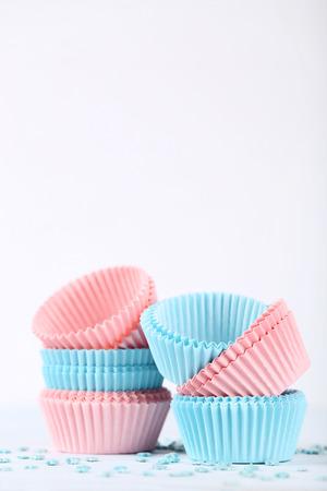 Estuches de cupcakes coloridos con chispitas sobre fondo blanco. Foto de archivo