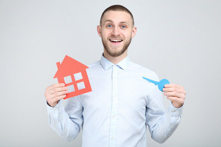 Young man with paper house and key on grey background Stock Photo