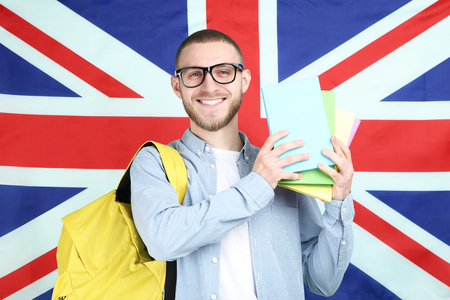 Młody człowiek z plecakiem i książkami na tle flagi brytyjskiej