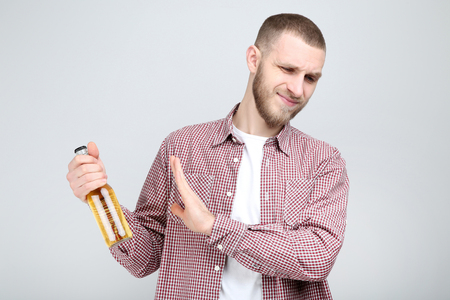 Young man with bottle of beer on grey background
