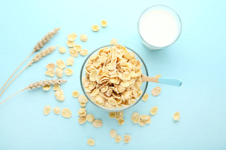 Corn flakes in bowl with glass of milk and wheat ears on blue background 版權商用圖片