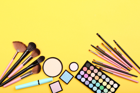 Makeup brushes with palette on yellow background