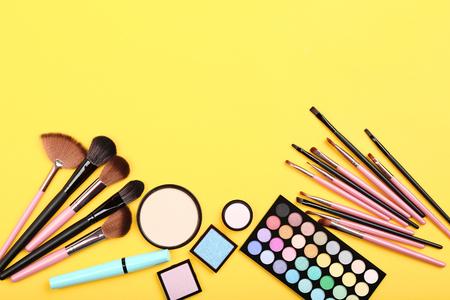 Pinceaux de maquillage avec palette sur fond jaune