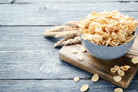 Corn flakes in bowl with wheat ears on grey wooden table Foto de archivo