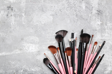 Set of makeup brushes on grey background